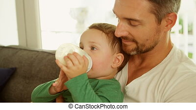 Boy in fathers lap drinking milk on sofa at home 4k -...