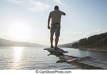 Boy in front of mountain lake