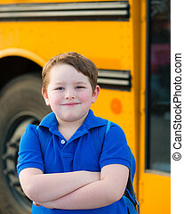Boy in front of school bus