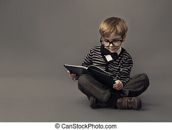 Boy in glasses reading book, smart little child study lesson, education concept