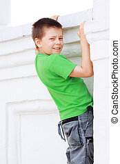Boy in green climbing on wall