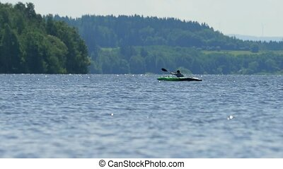 Boy in green kayak sail on pond. Sunny day on wonderful...