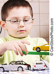 Boy in green playing with cars