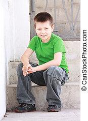 Boy in green sitting on steps