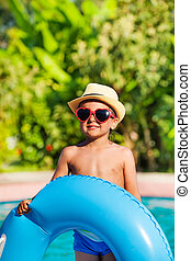 Boy in hat and sunglasses holding inflatable ring