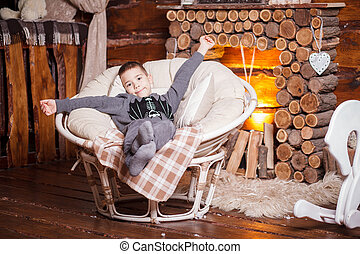Boy in hat sitting in chair Christmas tree and gifts
