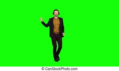 Boy in headphones listens to music, bounces on the spot. Green screen