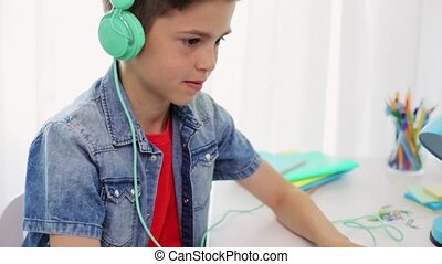 boy in headphones playing video game on laptop - technology,...