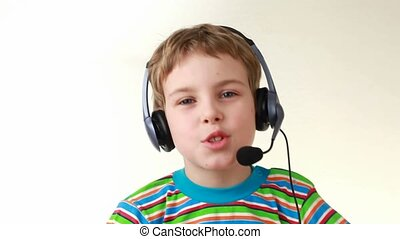 Boy in headset swings from side to side and sings