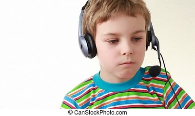 Boy in headset swings from side to side, shakes head, while listening music