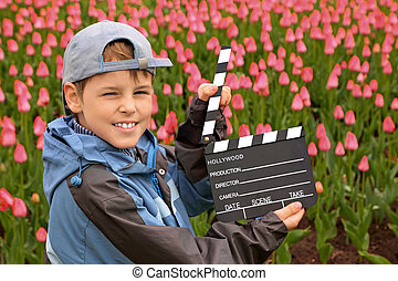 Boy in jacket and cap with cinema clapper board in their...