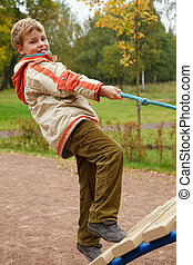 Boy in jacket is on playground in autumn park. Smiling, he climbs the stairs holding onto a rope.
