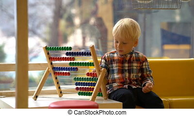 boy in kindergarten playing with abacus, against the window