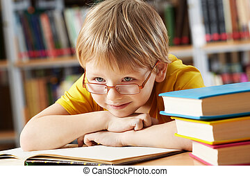Boy in library - Portrait of clever boy with open book in ...