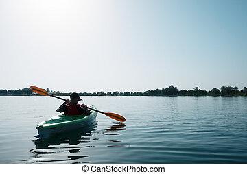 Boy in life jacket on green kayak