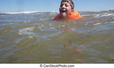 boy in lifejacket swim in sea with waves - Yong boy in...