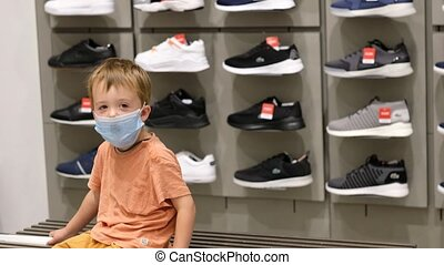 Little boy in medical mask looking at camera while sitting on bench near rack with sneakers in store during quarantine