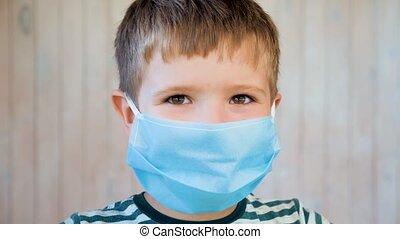Boy in medical facemask looking at camera. Coronavirus, ...