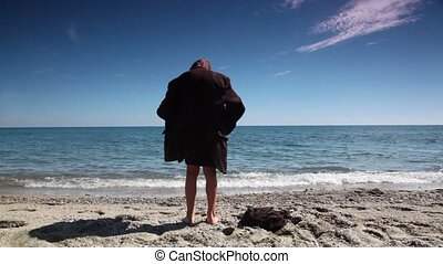 Boy in mens suit jacket stand back to camera on beach