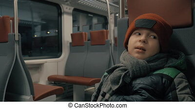 Boy in moving commuter train at night