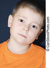 Boy in orange bending head
