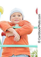 Boy in orange on climbing staircase