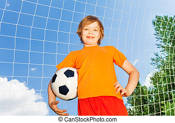Boy in orange T-shirt with football near woodwork