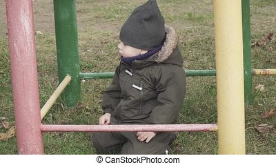 Boy in overalls on an old playground with rusty pipes in a city park