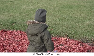 Boy in overalls plays on a flower bed covered with colored sawdust in a city park