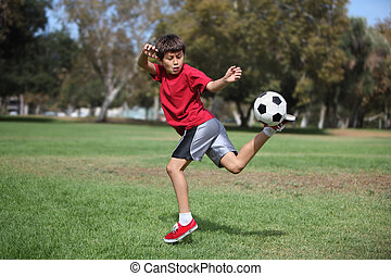 Boy in park kicking a soccer ball