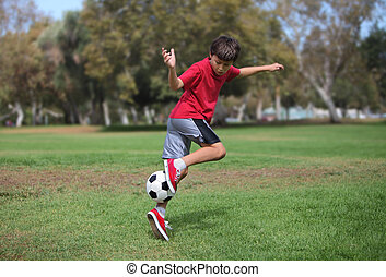 Boy in park kicking a soccer ball