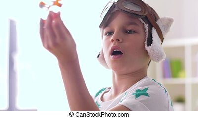 boy in pilot hat playing with airplane toy at home -...
