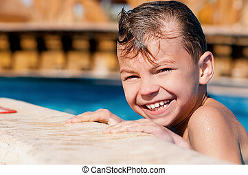 Boy in pool - Happy boy, relaxing on a swimming pool at aqua...