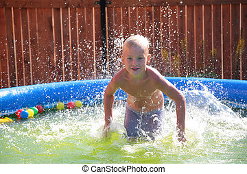 Boy in pool splashing