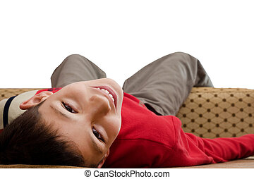 boy in red lying on sofa