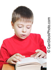 Boy in red reading book at desk