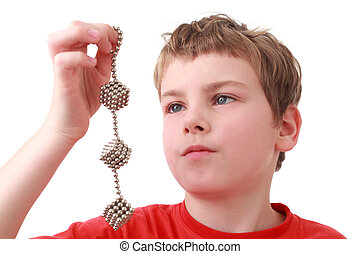 boy in red shirt keep cubes of metal balls isolated on white background