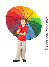 boy in red shirt with big multicolored umbrella standing on white and looking at side