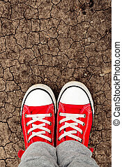 Boy in red sneakers standing on the ground, from above