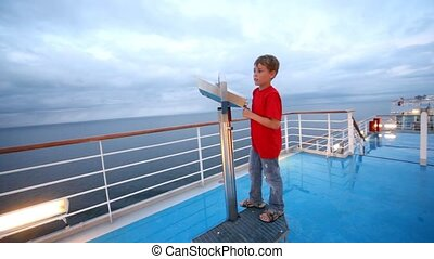 boy in red tee-shirt looks in field-glass on ship deck