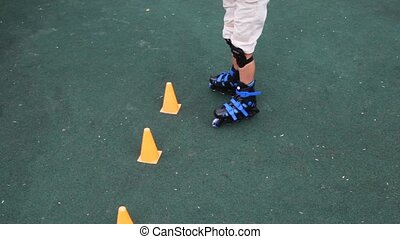boy in rollers puts counters on asphalt and passes between them