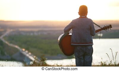 Boy in round glasses playing guitar in field in sunset and ...