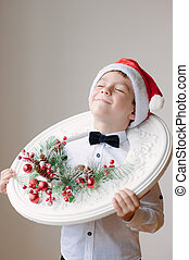 boy in Santa hat with Christmas decorations