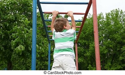 boy in shirt climbs down wall bars like monkey on playground...