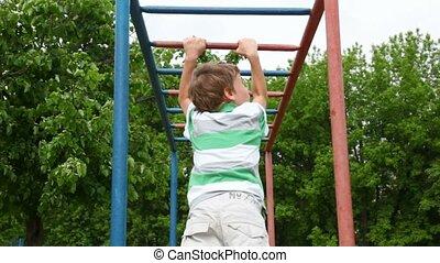 boy in shirt climbs down wall bars like monkey on playground