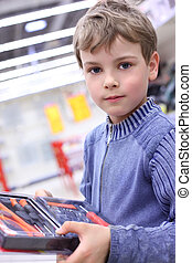 boy in shop with  tool set in hands