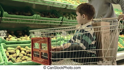 Boy in Shopping Cart - Cropped father driving his son in...