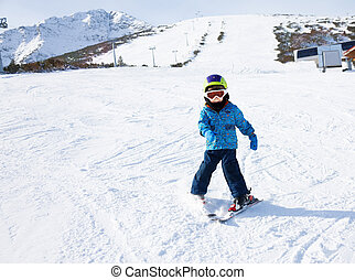 Boy in ski mask learns skiing on snow downhill