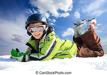 Boy lying in the snow in winter sports wear.