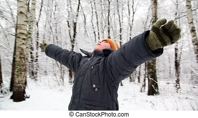 Boy in snow forest stretch hands looks up in sky